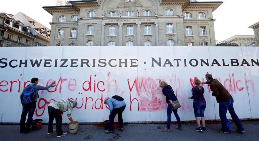 Medlemmer af »Uafhængige Penge Initiativet« også kaldet »Vollgeld« rydder op efter at have spraymalet et slogan på den schweiziske nationalbanks facade. Der stod »Kære Schweiziske Nationalbank, husk venligst, hvorfor vi grundlagde dig«. (Arkiv)