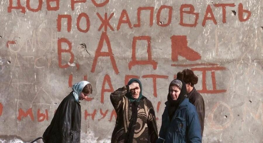 """En gruppe kvinder står i foran en mur i den tjetjenske hovedstad, Grozny, med påskriften """"Velkommen til helvede"""" i 2000 under den anden tjetjenske krig. Foto: Yuri Kochet/EPA"""