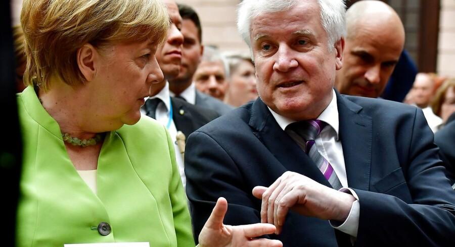 Tysklands indenrigsminister, Horst Seehofer, th., har givet kansler Merkel en frist på to uger til at opnå enighed om en EU-asylaftale. Dermed har formanden for et konservativt regionalparti i Bayern sat alt på ét bræt for at skabe et gennembrud i den store europæiske strid om flygtninge og migranter. Her sidder de to konservative ledere ved siden af hinanden ved fejringen af den internationale flygtningedag i onsdags.