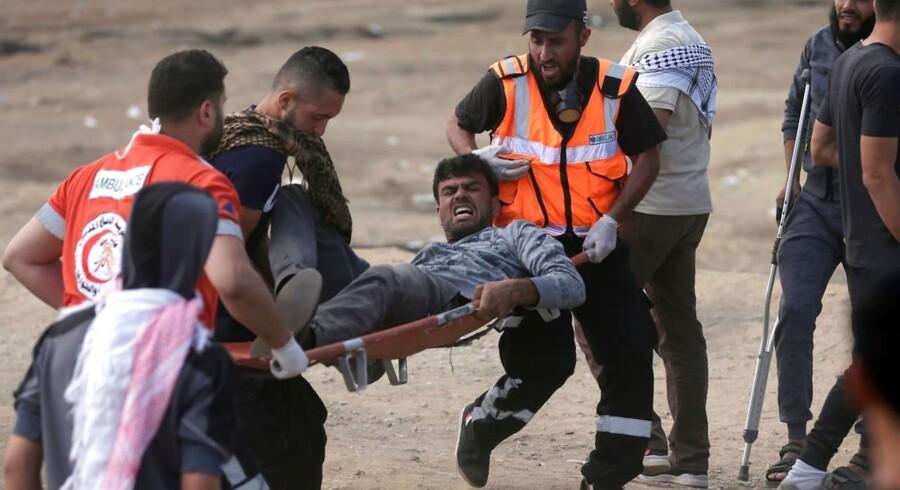 Palæstinensere bærer en demonstrant såret under sammenstødet med israelske styrker nær grænsen mellem Gaza og Israel øst for Gaza City, 14. maj 2018.