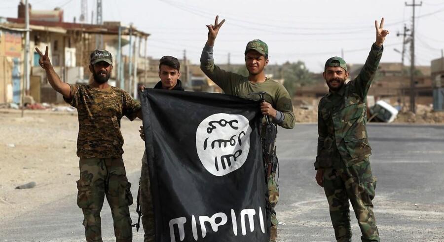 Irakiske medlemmer af Hashed al-Shaabi (Popular Mobilisation units) vender et IS-flag på hovedet i Al-Qaim den 3. november 2017. Irans præsident, Hassan Rouhani, erklærer ifølge Reuters, at Islamisk Stat er besejret. Det samme gør generalmajor Soleimani, chef for Irans revolutionære garde, skriver Ritzau tirsdag den 21. november 2017.. (Foto: AHMAD AL-RUBAYE/Scanpix 2017)