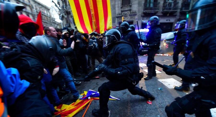 Det er kommet til sammenstød mellem politi og demonstranter i Barcelona, hvor tusinder søndag demonstrerer efter anholdelsen af den catalanske ekspræsident Carles Puigdemont.