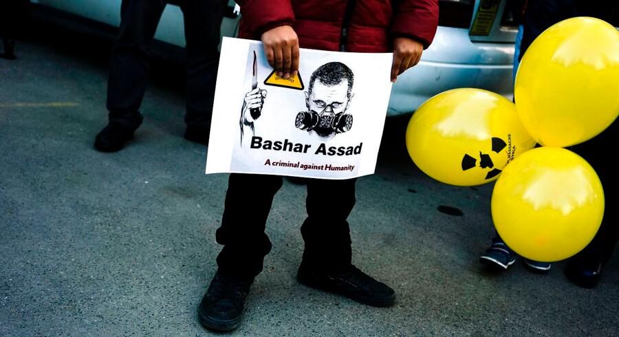 En syrisk immigrant viser et billede af Syriens leder Bashar al-Assad med gasmaske under demonstration foran den syriske ambassade i Sofia i Bulgarien. / AFP PHOTO / Dimitar DILKOFF