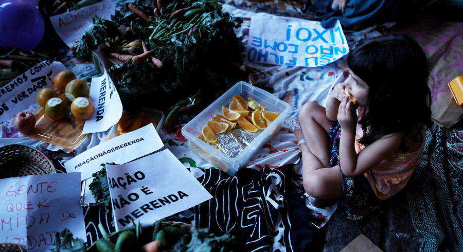 """A child eats an orange next to a sign reading """"Food Pellets are not meals"""" during a protest against Sao Paulo Mayor Doria's plans to serve school meals made of reprocessed food pellets in Sao Paulo, Brazil October 19, 2017. REUTERS/Nacho Doce"""