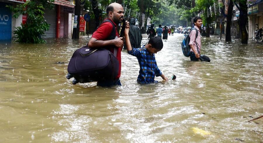 Indians wade through a flooded street during heavy rain showers in Mumbai on August 29, 2017. Årets monsunsæson i Asien har ført til de værste oversvømmelser i Indien, Nepal og Bangladesh i årevis. Nødhjælpsorganisationer advarer om en humanitær krise. Det skriver Ritzau onsdag den 30. august 2017. (Foto: PUNIT PARANJPE/Scanpix 2017)