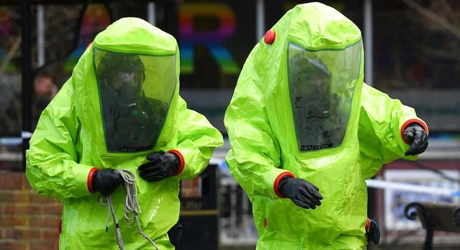 Ansatte fra den britiske beredskabstjeneste i grønne sikkerhedsdragter arbejder ved den bænk, hvor eksagenten Sergej Skripal og hans datter blev forsøgt myrdet i det sydlige England med en kraftig nervegift.