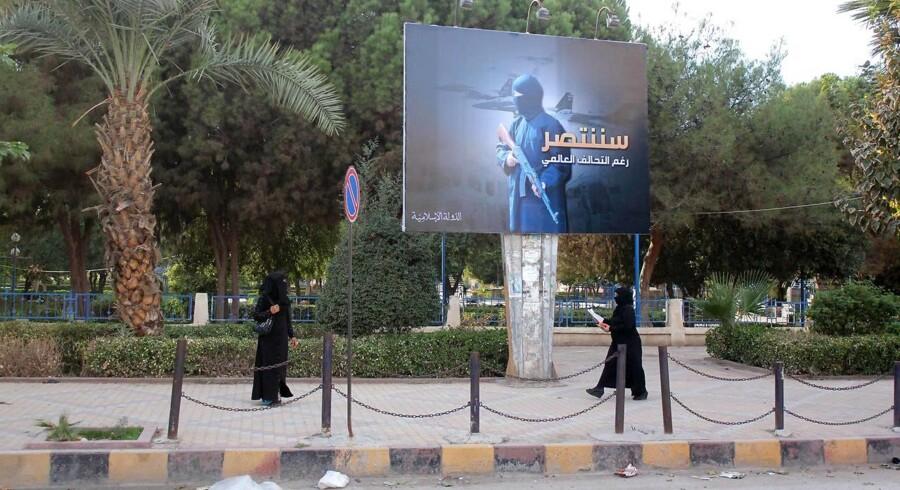 I den syriske by Raqqa, der er en højborg for Islamisk Statgår kvinder i 2014 under en propagandaplakat med teksten »Vi vil vinde trods den internationale koalition«.