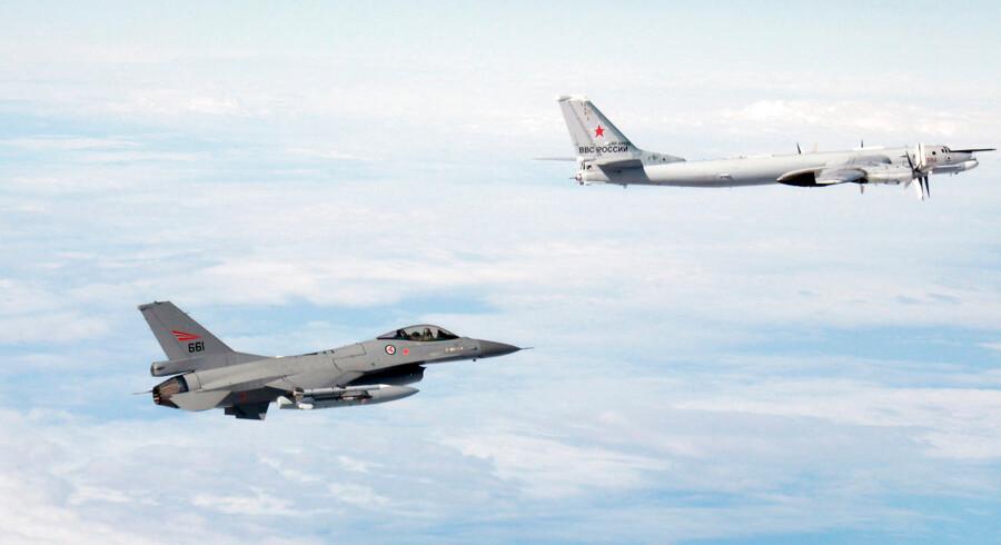 Arkivfoto: Et russisk Tupolev TU-95-militærfly (til højre) følges af et norsk F-16-fly under en militærøvelse.