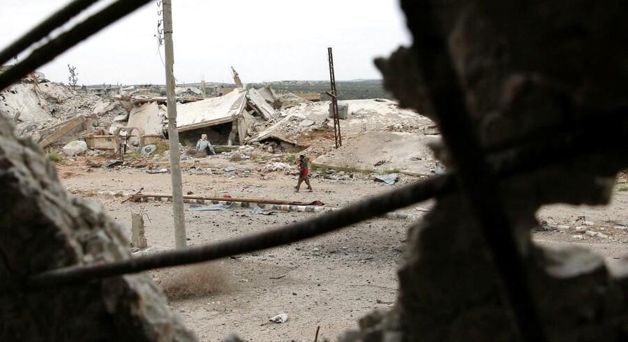 Billede fra Deraa i Syrien, hvor folk går langs en ødelagt vej.