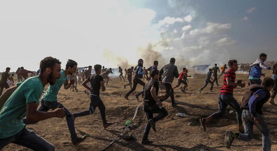 Palæstinensere løber væk fra tåregas efter sammenstød ved grænsen mellem Israel og Gaza-striben. Foto: Mohammed Saber/EPA/Ritzau Scanpix