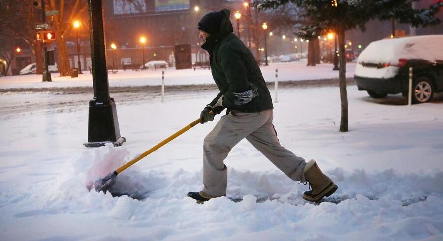 En mand skovler sne i New York. Byens skoler er lukket og den offentlige transport forstyrret. NEW YORK, MARCH 14