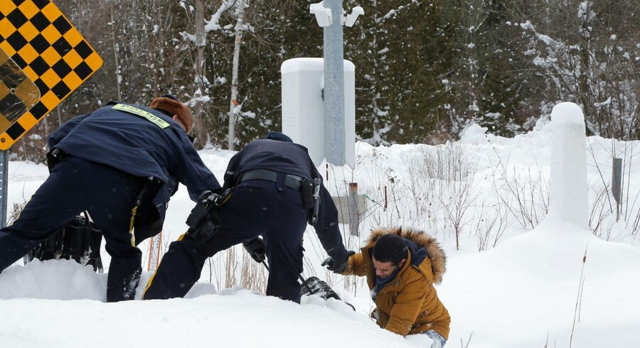 A man who told police that he was from Mauritania is helped up a hill and taken into custody by Royal Canadian Mounted Police (RCMP) officers after walking across the U.S.-Canada border into Hemmingford, Quebec, Canada February 13, 2017. Picture taken February 13, 2017. REUTERS/Christinne Muschi