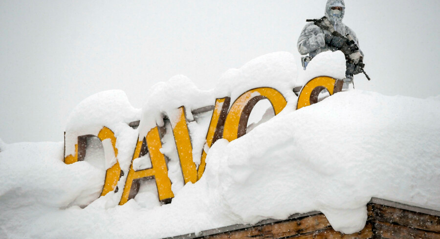 "An armed security personnel wearing camouflage clothing stands on the rooftop of a hotel, next to letters covered in snow reading ""Davos"", near the Congress Centre ahead of the opening of the 2018 World Economic Forum (WEF) annual summit on January 22, 2018 in Davos, eastern Switzerland. The World Economic Forum (WEF) runs through January 23 - 26, focusing this year on the theme ""Creating a Shared Future in a Fractured World"". / AFP PHOTO / Fabrice COFFRINI"