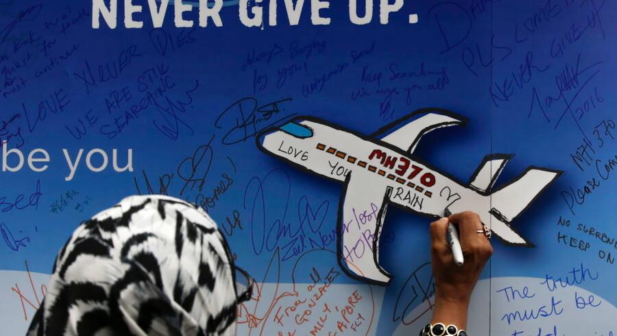 En kvinde skriver en besked til de savnede passagerer fra MH270 på et banner under en mindehøjtidlighed i Kuala Lumpur.