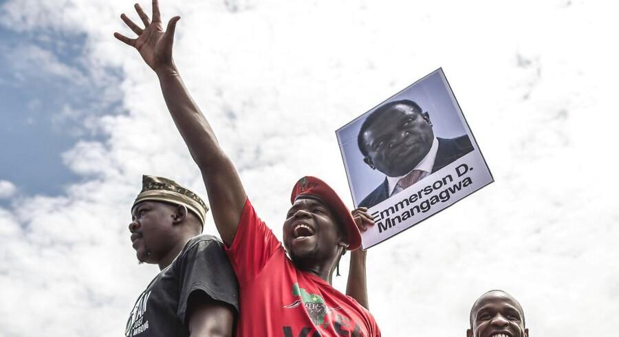 Studerende ved universitet i Zimbabwes hovedsatd, Harare, svinger med et portræt af landets formentlig kommende præsident, Emmerson Mnangagwa, under en demonstration mandag. / AFP PHOTO / -