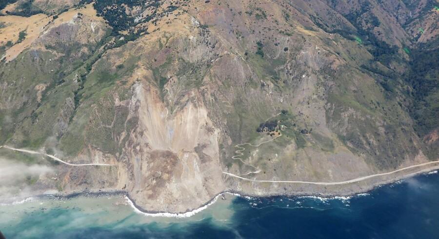 Billedet viser, hvordan en stor del af Highway 1 er dækket af mudder og jord.