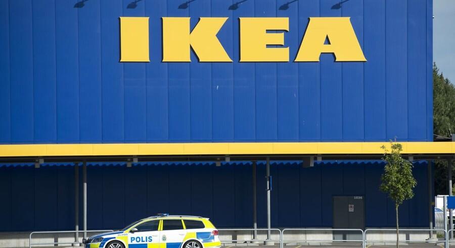 En politibil foran det Ikea-varehus, hvor to mennesker i mandags blev dræbt af en afvist asylansøger. Drabene har fået debatten om Sveriges indvandringspolik til at rase.