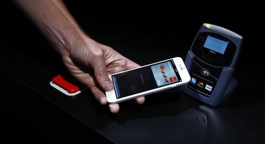 Det ser altid nemt ud, når det demonstreres på en scene. Apples mobilbetalingstjeneste Apple Pay fungerer ved at holde telefonen hen til kasseterminalen og så trykke på en knap, så ens fingeraftryk læses, og betalingen godkendes. Men mulighederne for at bruge Apple Pay er begrænset - og langtfra alle Apple-brugere kan være med. Foto: Monica Davey, EPA/Scanpix
