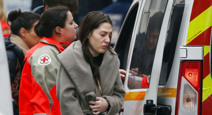 En grædende kvinde uden for Charlie Hebdos kontor i Paris hjælpes ind i en ambulance.