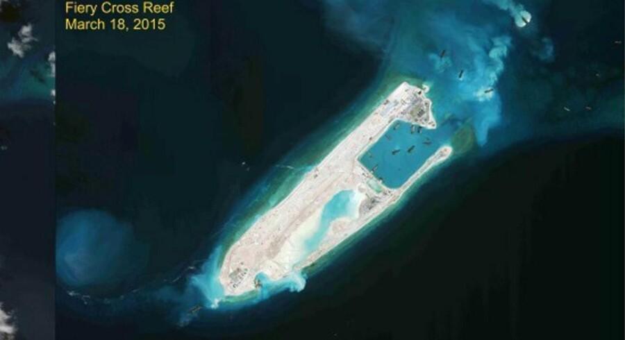 Kina opruster militært og gør territorielle krav i Det Sydkinesiske Hav. Her ses udviklingen på revet Fiery Cross, som til venstre er fotograferet fra luften 14. august 2014, og til højre ses det, hvordan der 18. marts 2015 er læsset sand på revet som et middel til, at Kina kan gøre krav på øen. På denne måde udvider Kina sine søgrænser, mens sårbare dyre- og plantearter trues af, at deres levesteder bliver ødelagt. Foto: Reuters