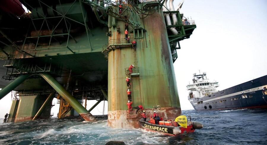 Greenpeace-aktivister kravler op på boreriggen Leiv Eiriksson ud for den grønlandske kyst i 2011. Det koster nu organisationen en rekordstor bøde. Arkivfoto.
