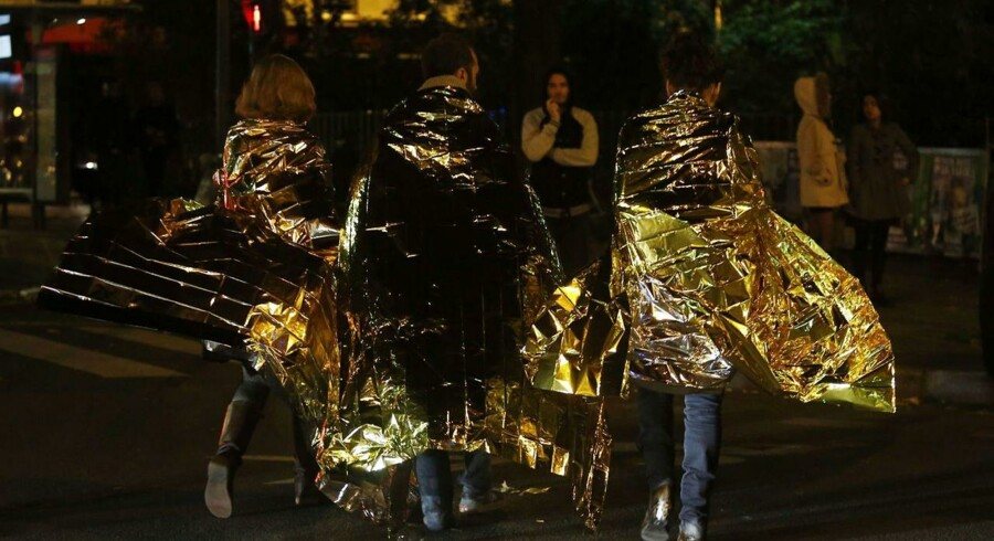 People wrapped in life emergency blankets walk near the Bataclan concert hall in central Paris, early on November 14, 2015. At least 120 people were killed in a series of terror attacks in Paris on November 13 according to a provisional total, a source close to the investigation said. AFP PHOTO / FLORIAN DAVID