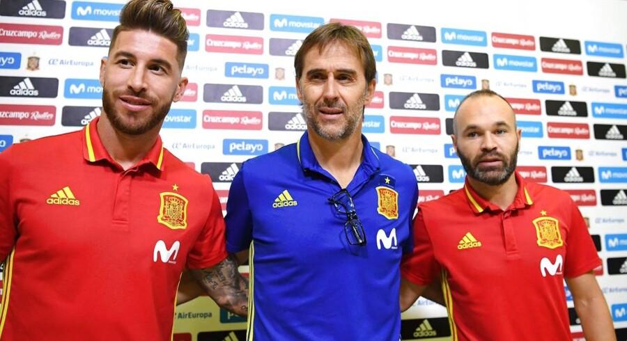 Julen Lopetegui flankeret af landsholdsveteranerne Sergio Ramos og Andrés Iniesta, der også - og nok så vigtigt - var anførere for henholdsvis Real Madrid og FC Barcelona i den forløbne sæson. Kan man stole på, at hovedstadsklubbens kommende træner vil dele sol og vind lige på et nationalmandskab, der i forvejen har begrænset støtte i store dele af befolkningen? Det spanske fodboldforbund mener nej.