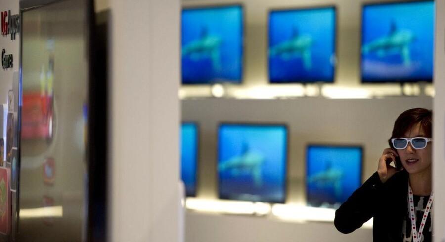 3D er stadig det helt store - og TV-producenternes adgang til at sælge et nyt fjernsyn som erstatning for det, der blev købt for nylig uden 3D. Her ser en kvinde på LGs udvalg på den store elektronikmesse, IFA, i Berlin. Foto: Odd Andersen, AFP/Scanpix