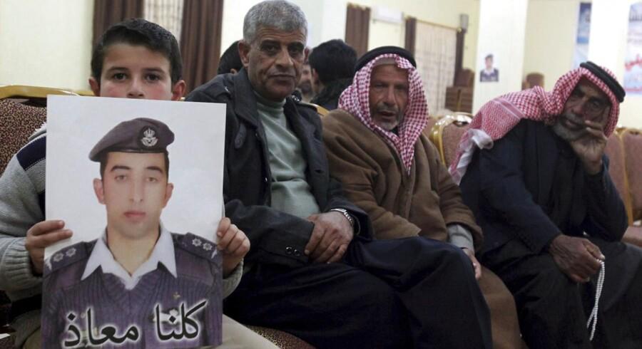 Familiemedlemmer til den tilfangetagne pilot viser et billede af gidslet frem. Foto: Ahmad Abdo