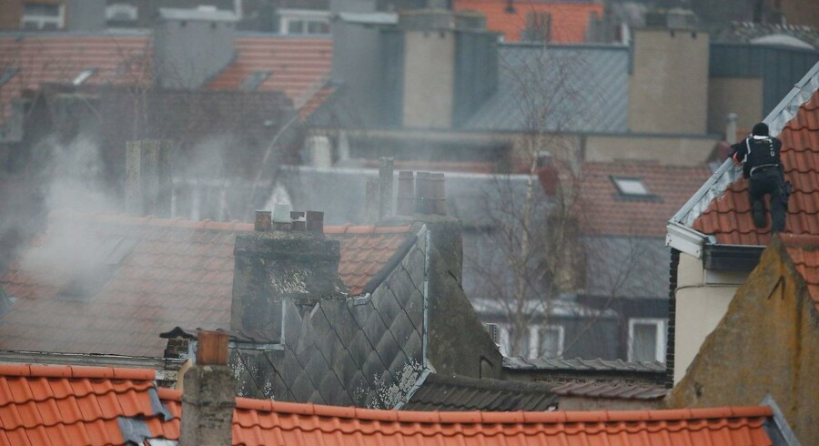 epa05213146 A police officer takes position as smoke comes out of the rooflight of a house where a suspect is believed to be holed up during a police operation in Forest, Brussels, Belgium, 15 March 2016. According to reports, police have stormed a flat where a suspected Islamist was hiding after a manhunt. The police operation took place after shots were fired in Brussels during an anti-terror raid linked to the 13 November Paris Attacks. At least two officers were slightly injured, police said. The French Interior Minister confirmed that French Police were taking part in the operation alongside their Belgian colleagues. EPA/LAURENT DUBRULE
