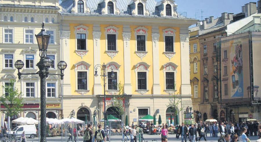 Krakow besøges årlig af to millioner turister, så selv om der er mange hestevogne i byen (t.h.), er der nok kunder. En gademusikant (t.v.) klædt ud i en traditionel dragt. Dem ser man mange af i Krakow.
