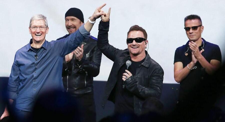 Apple-topchef Tim Cook (til venstre), da han 9. september annoncerer, at alle iTunes-brugere får et gratis album med den irske rockgruppe U2, som her ses på scenen med forsanger Bono (nr. 2 fra højre), The Edge (nr. 2 fra venstre) og Larry Mullen Jr. Foto: Justin Sullivan, Getty/AFP/Scanpix