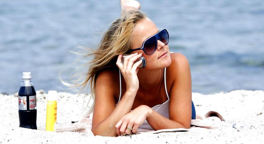 Kvinde taler i mobiltelefon på stranden. Mobiltelefon med på ferie.