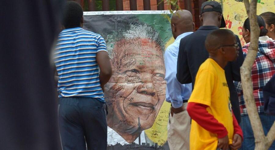Sydafrikanere sætter deres underskrift på en Mandela-plakat i Soweto fredag.