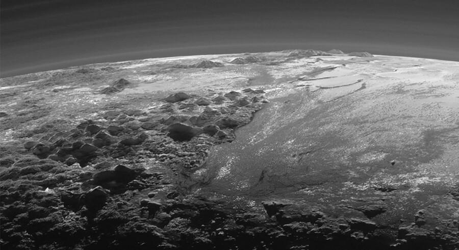 Der er vidtstrakte sletter, gletsjere og en lavtliggende dis i den tynde og svagt oplyste atmosfære over dværgplaneten Pluto. Foto: NASA