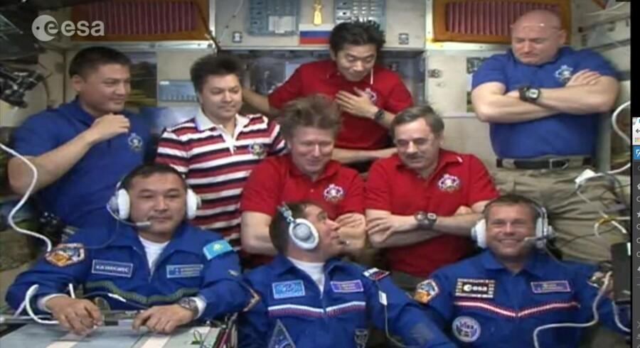 Der sidder ni mand på en rumstation ...Forrest sidder Aidyn Aimbetov, 43, Sergej Volkov, 42, og og en storsmilende Andreas Mogensen, 38, få minutter efter at de er kravlet ind i rumstationen efter mere end to døgn i det trange Sojuz-fartøjBag dem står i mere afslappet påklædning den nuværende besætning på ISS: Fra venstre mod højre: Kjell Norwood Lindgren, der trods sit svenske navn er amerikaner, men født i Taiwan. Han er 42 år gammel og på sin først rummission. Oleg Kononenko er russer, 51 år gammel, og på sin tredje rummission. Kommandør Gennady Padalka er 57 år, fra Rusland, og på sin femte rummission. Kimiya Yui, er japaner, 45 år gammel og på sin første mission. Næstkommanderende, Mikhail Kornijenko, er 55 år, fra Rusland og på sin anden rummision. Scott Kelly er amerikaner, er 51 år gammel og på sin fjerde rummission.De to sidste skal være på rumstationen i et helt år.