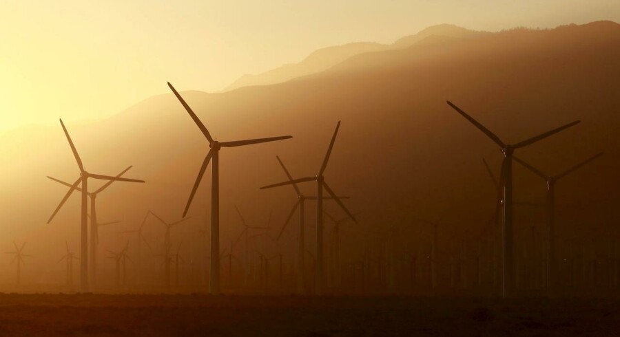 A windmill farm is seen in front of smoke from the Lake Fire in the San Bernardino National Forest, seen at sunset from Palm Springs, California June 18, 2015.