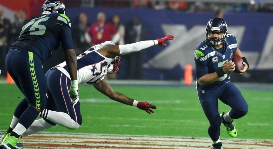 Quarterback Russell Wilson of the Seattle Seahawks, eludes the tackle of a New England Patriots defender during Super Bowl XLIX February 1, 2015 at the at University of Phoenix Stadium in Glendale, Arizona. The Patriots defeated the Seahawks 28-24. AFP PHOTO / TIMOTHY A. CLARY