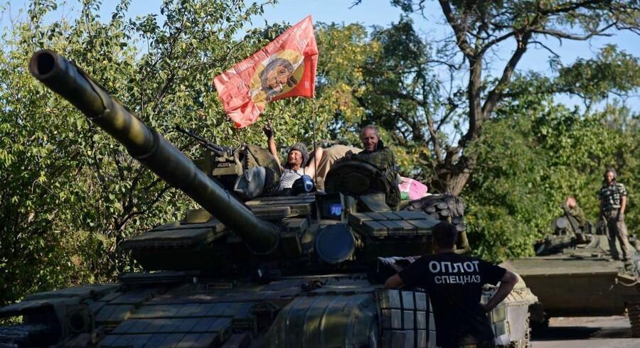Prorussiske oprørere hviler ud oven på en af deres tanks sydøst for Donetsk.