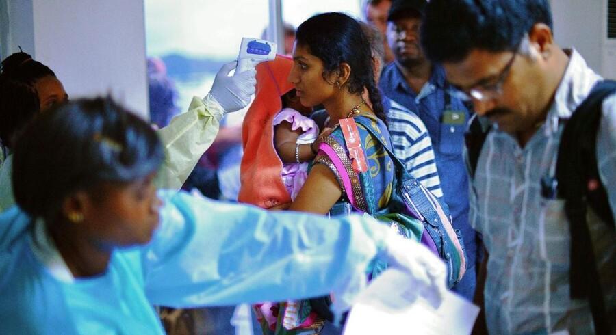 Ankommende passagerer får taget temperaturen i Sierra Leones internationale lufthavn. Ifølge WHO har det nuværende udbrud af ebola kostet 1.013 menneskeliv.