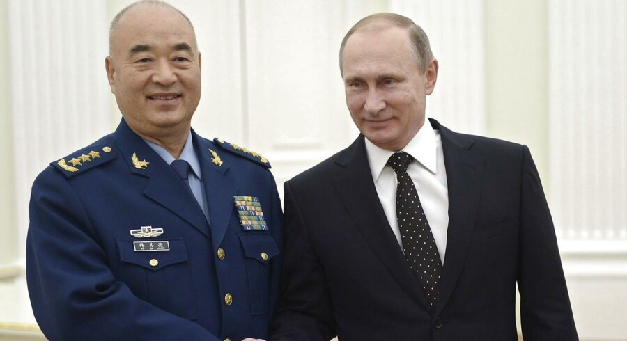Vladimir Putin trykker hånd med vicebestyrelsesformand for Kinas militærkommission, Xu Qiliang, under et møde i Kremlin