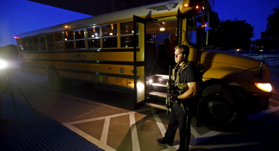 A police officer stands near a school bus used to evacuate attendees of the Muhammad Art Exhibit and Contest sponsored by the American Freedom Defense Initiative after a shooting outside the Curtis Culwell Center where the event was held in Garland, Texas May 3, 2015. Two gunmen who opened fire on Sunday at the anti-Islam art exhibit near Dallas featuring depictions of the Prophet Mohammad were themselves shot dead at the scene, a local CBS television affiliate and other local media reported, citing police. REUTERS/Mike Stone TPX IMAGES OF THE DAY