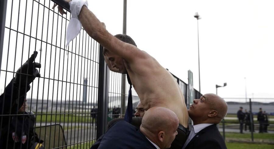 Det franske flyselskabs HR-direktør måtte eskorteres væk og kravle over høje hegn, efter flere hundrede vrede franske fagforeningsfolk invaderede flyselskabets kontorer i protest mod nedskæringsplaner. Se billederne her.Vice-HR-direktør i Air France, Xavier Broseta, forsøger at kravle over et hegn med hjælp fra politi og sikkerhedsfolk.