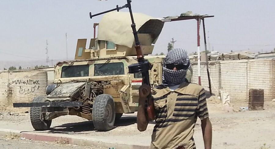 En oprører fra den militante islamistiske milits ISIS stod torsdag vagt nær den irakiske by Baiji nord for Bagdad. Netop ISIS volder nu problemer for USA, idet Iraks premierminister, Naouri al-Maliki, har bønfaldet amerikanerne om at hjælpe ham i kampen mod militsen. Spørgsmålet er nu, om man kan tillade sig at støtte Iraks leder, mens man forsøger at sende Syriens leder ud i kulden. Foto: Reuters