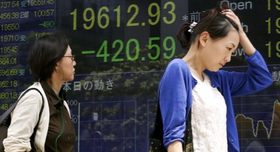 I Tokyo tog en fodgænger sig til hovedet, da hun passerede den japanske børs informationstavle fredag morgen. De japanske kurser faldt markant med 2,10 pct.