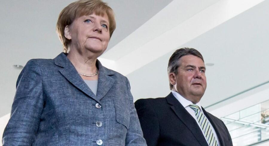 Sigmar Gabriel og kansler Angela Merkel undervejs til pressekonference i regeringskomplekset i Berlin. Foto: Michael Kappler/EPA