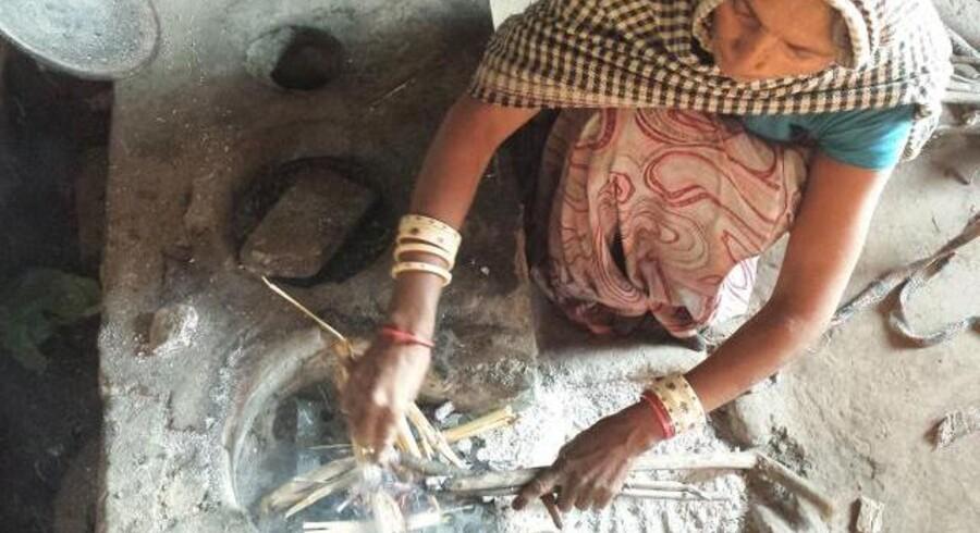 En kvinde tænder op i et åbent ildsted af den traditionelle slags, som bruges overalt i Indiens fattige landområder. Under brændet anes den hullede metalplade, som kan mindste mængden af røg.