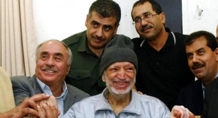 Palæstinas daværende præsident Yasser Arafat smiler her til kameraet omgivet af sine egyptiske og tunesiske læger den 28. oktober 2004 i Ramallah. 11. november døde han på et hospital i Paris, hvortil han var taget for at få behandling for sin uforklarlige og pludseligt opståede sygdom.
