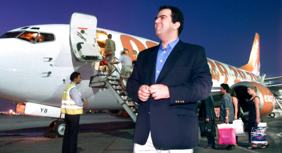 """EasyJet tycoon Stelios Haji-Ioannou smiles in front of one of his jets 19 September 2000 on the tarmac at Athens international airport. The low budget airline has recently ordered 32 new aircraft to add to the fleet of 18 existing Boeing 737-300 jets. Stelios Haji-Ioannou other """"Easy"""" businesses are internet shops opening around the world and a rent-a-car company. Owner of the no-frills airline, the Athens-born Cypriot millionaire, who is based in Britain, Haji-Ioannou was in 2000 named by The Sunday Times as Britain ´s 44th richest man, with a business empire valued at 500 million pounds (700 million dollars) (ELECTRONIC IMAGE)"""