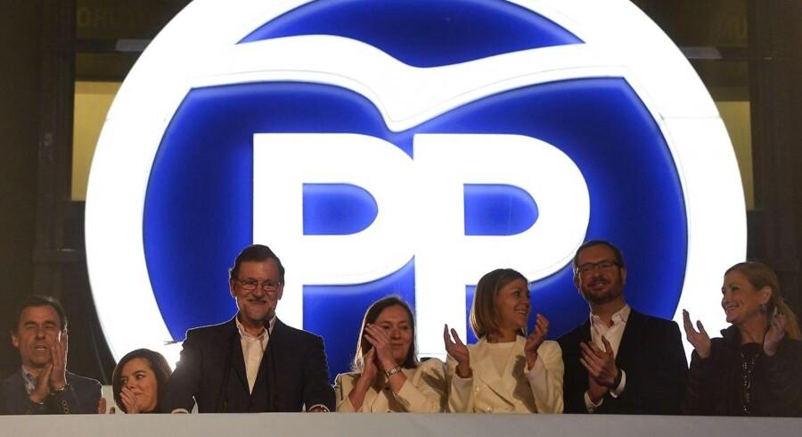 Efter søndagens spanske valg havde de fremmødte PP-tilhængere trods markant tilbagegang lejlighed tiljuble premierminister Mariano Rajoy (nummer tre fra venstre), som var flankeret af sin hustru og ledende partifæller udenfor hovedkvarteret i det centrale Madrid, hvor de fremmødte imidlertid måtte vente til den anden side af midnat, før premierministeren havde fundet en grimasse og et budskab, der kunne passe til at bevæge sig ud på partibygningens berømte balkon.